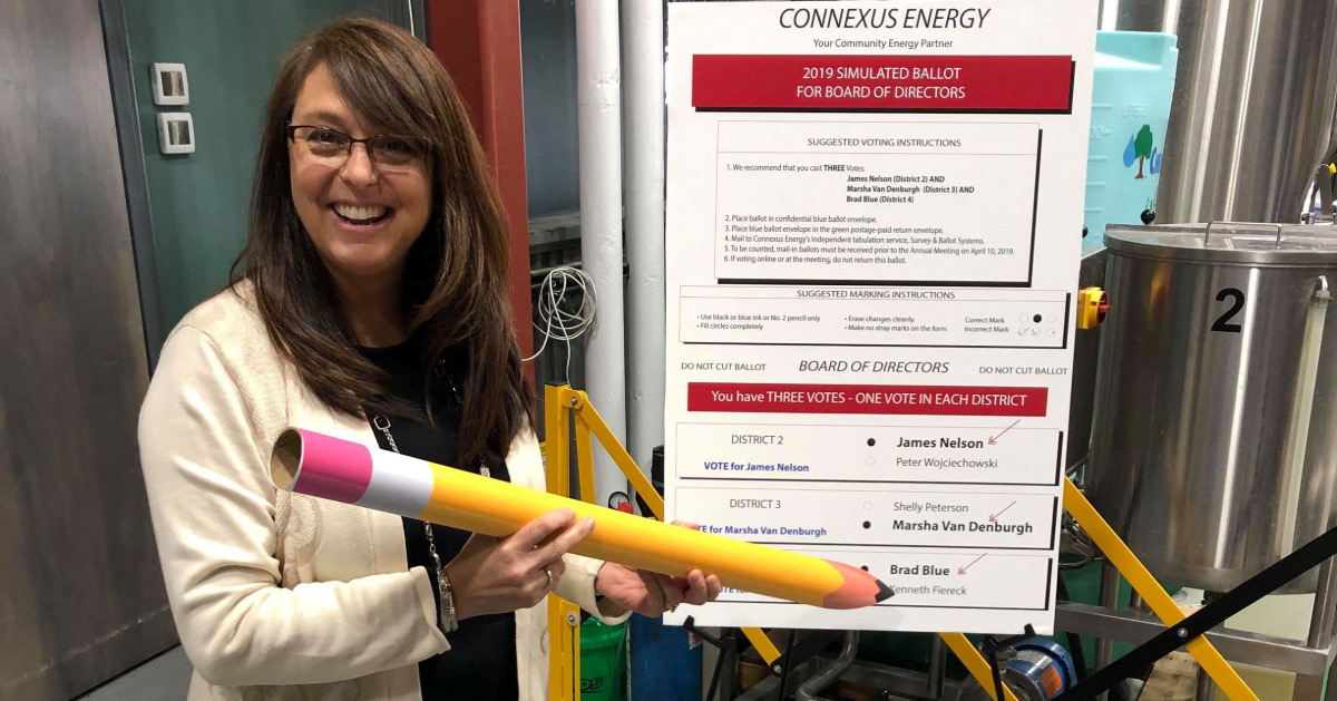 A woman holding an oversized pencil with the simulated Connexus ballot